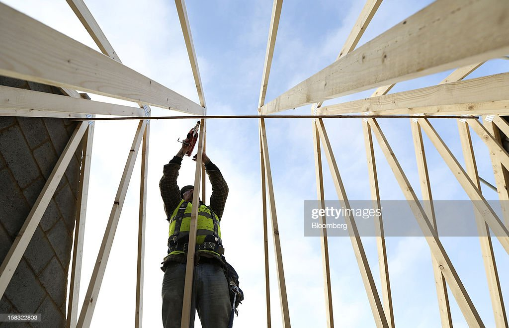 A builder assembles the wooden roofing joists in a new home at a Barratt Developments Plc construction site for residential housing in Bedford, U.K., on Thursday, Dec. 13, 2012. Barratt Developments Plc, the U.K.'s largest homebuilder by volume, said advance sales rose 21 percent as government initiatives to boost homebuilding lifted private reservations in the autumn selling season. Photographer: Chris Ratcliffe/Bloomberg via Getty Images