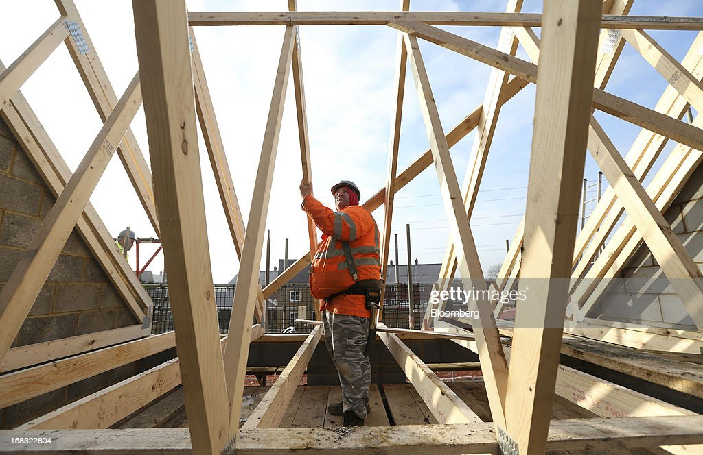 A builder assembles wooden roofing joists on a new home at a Barratt Developments Plc construction site for residential housing in Bedford, U.K., on Thursday, Dec. 13, 2012. Barratt Developments Plc, the U.K.'s largest homebuilder by volume, said advance sales rose 21 percent as government initiatives to boost homebuilding lifted private reservations in the autumn selling season. Photographer: Chris Ratcliffe/Bloomberg via Getty Images