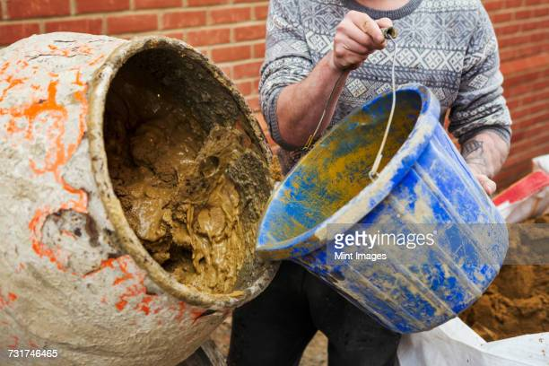 A builder, bricklayer standing next to a cement mixer, holding a blue bucket.