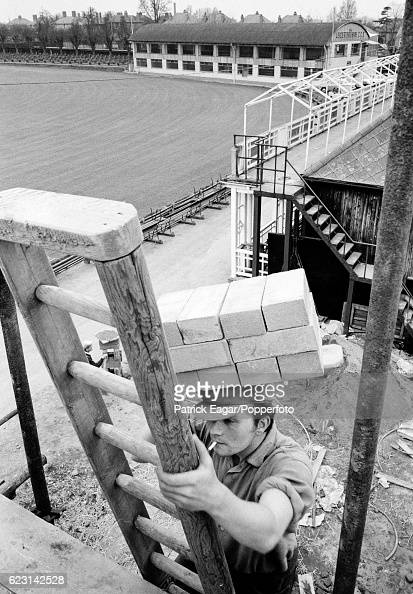 A builder carries bricks up a ladder during the construction of the new Pavilion at Grace Road Leicester circa March 1966