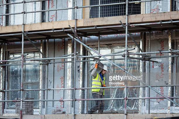 A builder carries materials he works on the 'Catford Green' residential apartment complex during construction by Barratt Developments Plc in the...