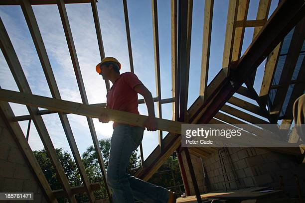 Builder carrying roof joist in unfinished house