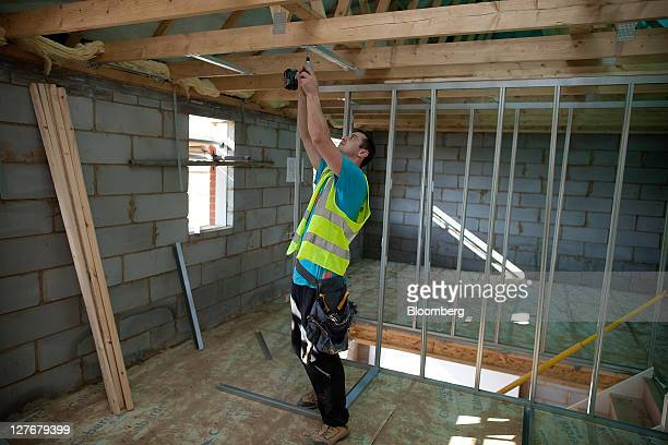 A builder fits a stud wall inside a new home at Bovis Homes Group Plc's Kingsmere residential development in Bicester UK on Friday Sept 30 2011 UK...