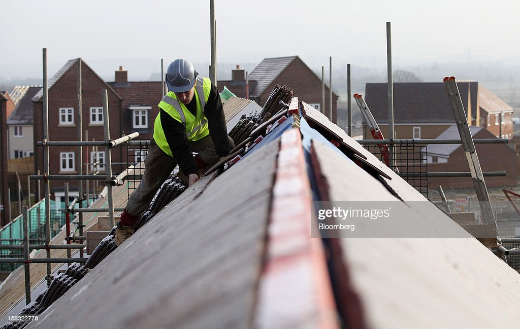 A builder fixes a roof tile into position on the roof of a new home at a Barratt Developments Plc construction site for residential housing in Bedford, U.K., on Thursday, Dec. 13, 2012. Barratt Developments Plc, the U.K.'s largest homebuilder by volume, said advance sales rose 21 percent as government initiatives to boost homebuilding lifted private reservations in the autumn selling season. Photographer: Chris Ratcliffe/Bloomberg via Getty Images