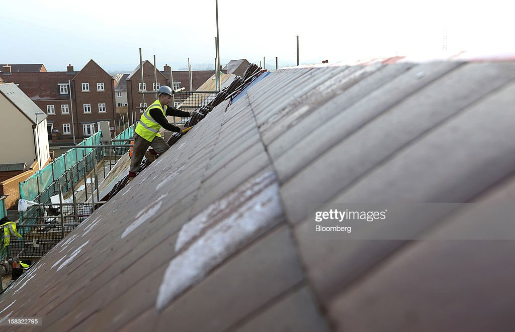 A builder fixes tiles to the roof of a new home at a Barratt Developments Plc construction site for residential housing in Bedford, U.K., on Thursday, Dec. 13, 2012. Barratt Developments Plc, the U.K.'s largest homebuilder by volume, said advance sales rose 21 percent as government initiatives to boost homebuilding lifted private reservations in the autumn selling season. Photographer: Chris Ratcliffe/Bloomberg via Getty Images