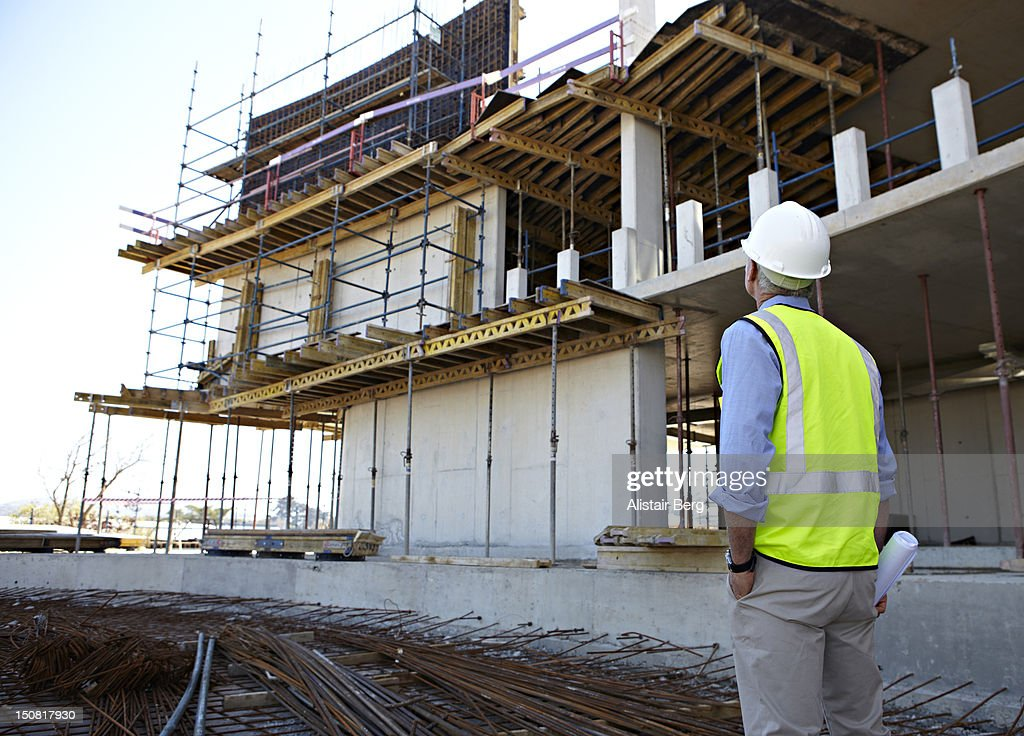 Builder looking at unfinished office block : Stock Photo