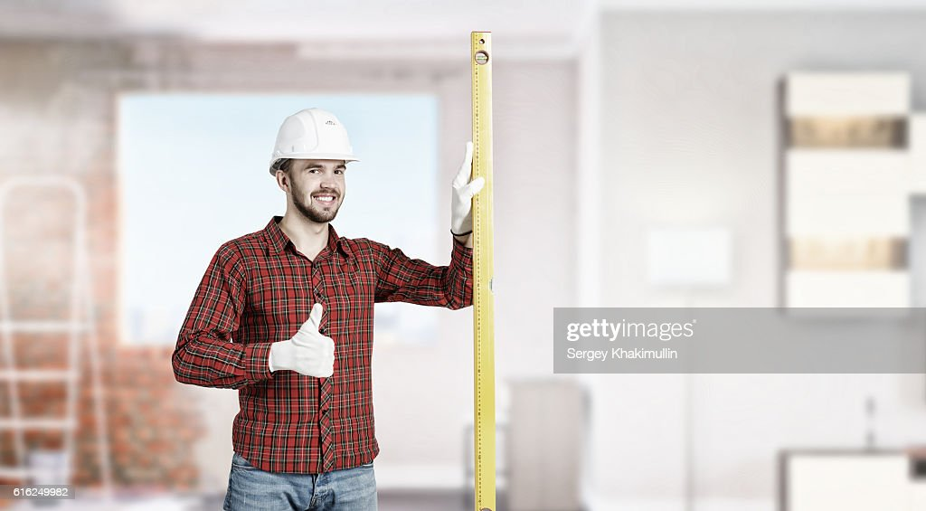 Builder man with level . Mixed media : Stock Photo