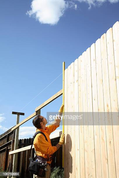 Builder measures wooden fence.