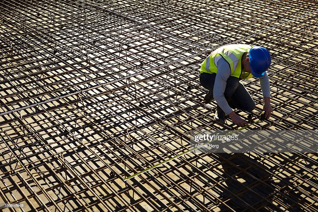 Builder measuring reinforcing rods : Stock Photo