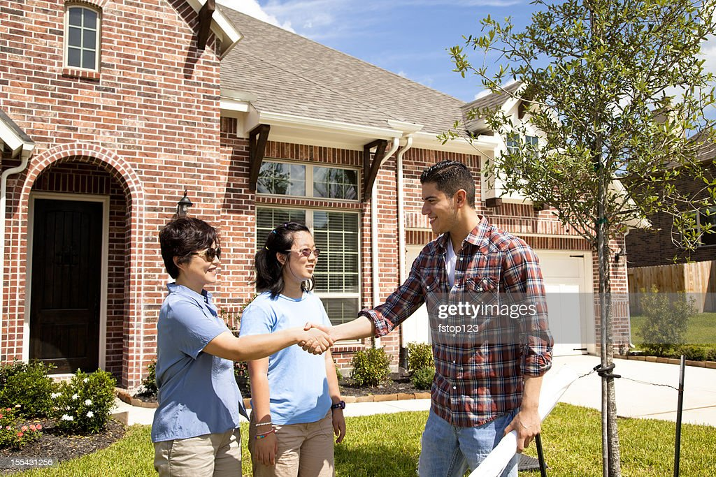 Builder meeting with woman and daughter at new home : Stock Photo