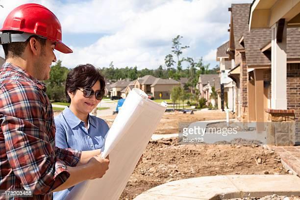 Builder Gespräch mit Frau in neues Zuhause-Konstruktion