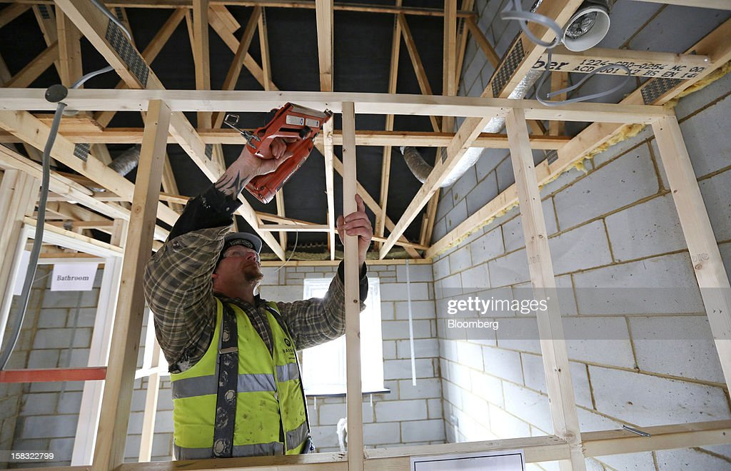A builder nails a wooden strut to a partition wall frame inside a new home at a Barratt Developments Plc construction site for residential housing in Bedford, U.K., on Thursday, Dec. 13, 2012. Barratt Developments Plc, the U.K.'s largest homebuilder by volume, said advance sales rose 21 percent as government initiatives to boost homebuilding lifted private reservations in the autumn selling season. Photographer: Chris Ratcliffe/Bloomberg via Getty Images