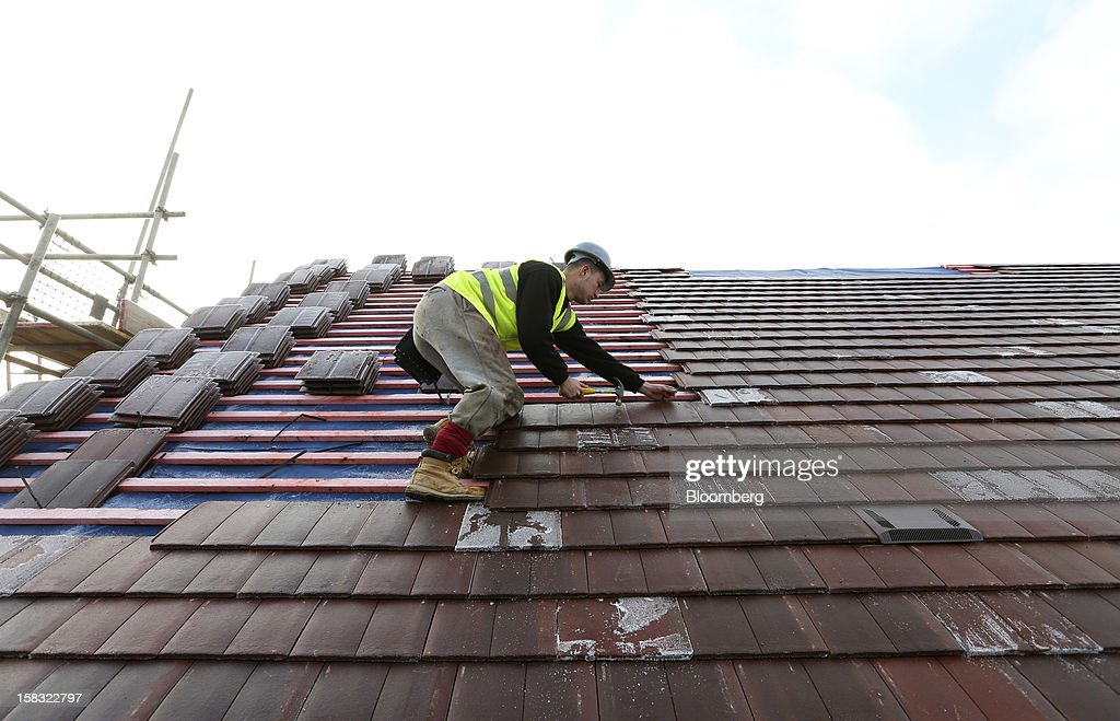 A builder nails tiles to the roof of a new home at a Barratt Developments Plc construction site for residential housing in Bedford, U.K., on Thursday, Dec. 13, 2012. Barratt Developments Plc, the U.K.'s largest homebuilder by volume, said advance sales rose 21 percent as government initiatives to boost homebuilding lifted private reservations in the autumn selling season. Photographer: Chris Ratcliffe/Bloomberg via Getty Images