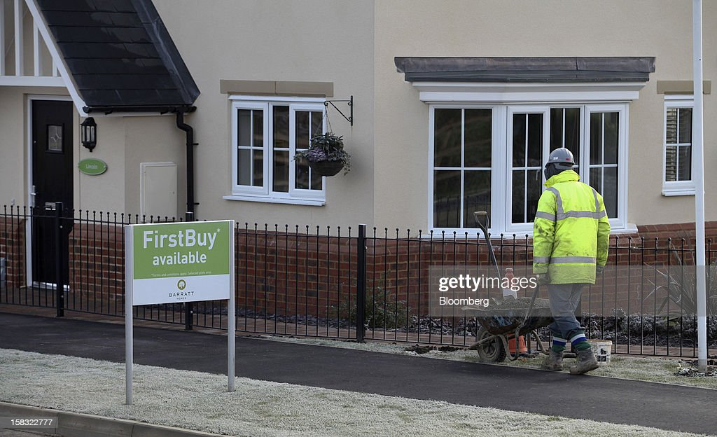 A builder pushes a wheelbarrow past a completed home at a Barratt Developments Plc construction site for residential housing in Bedford, U.K., on Thursday, Dec. 13, 2012. Barratt Developments Plc, the U.K.'s largest homebuilder by volume, said advance sales rose 21 percent as government initiatives to boost homebuilding lifted private reservations in the autumn selling season. Photographer: Chris Ratcliffe/Bloomberg via Getty Images