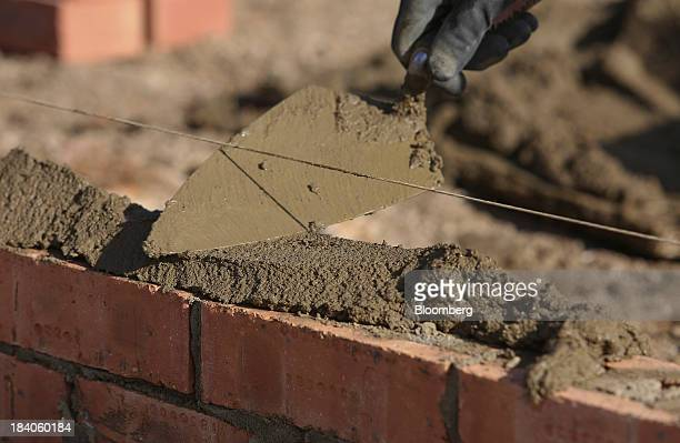 A builder trowels mortar as he prepares to lay a row of bricks on a new residential home during construction at a Bellway Plc real estate site in...