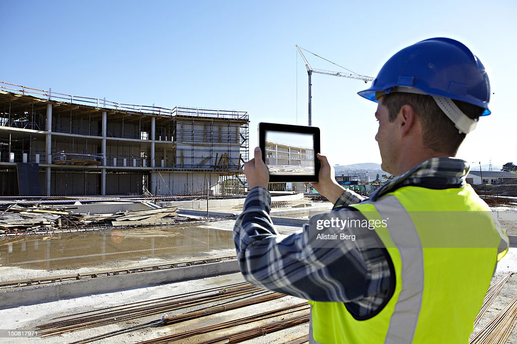 Builder using camera in tablet computer : Stock Photo