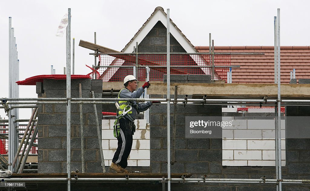 A builder walks along scaffolding outside a house during construction at a Persimmon Plc residential housing site in South Ockenden, U.K., on Friday, Aug. 16, 2013. Persimmon, the largest homebuilder by market value, said in July that its operating margin widened to about 15 percent during the half from 12.1 percent. Photographer: Chris Ratcliffe/Bloomberg via Getty Images