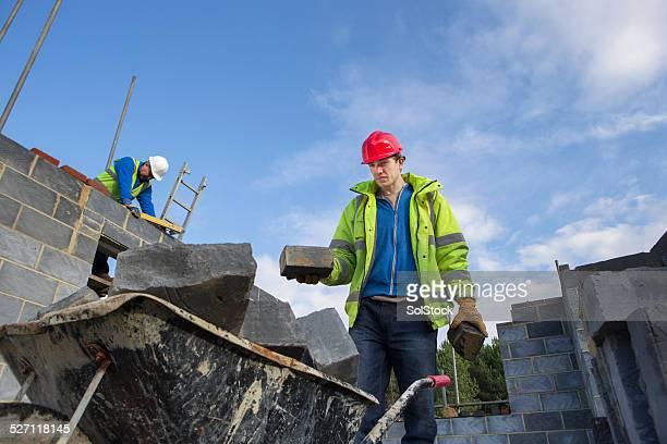 Builder with a Wheel Barrow of Bricks