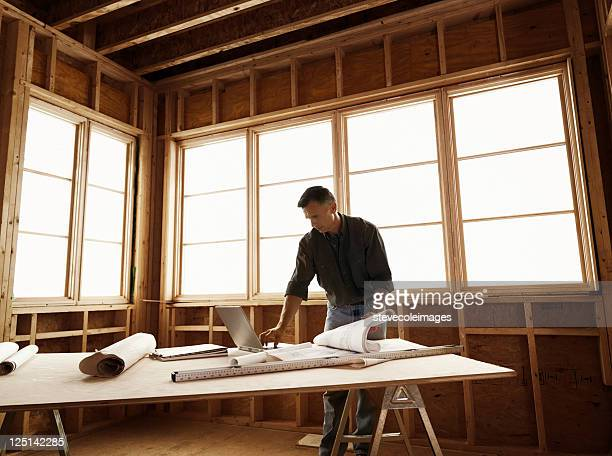 Builder with Blueprints on Plywood Table