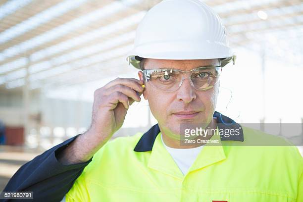 Builder with safety glasses inserting earplugs on construction site