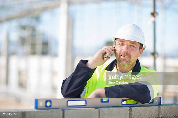 Builder with spirit level on construction site chatting on smartphone