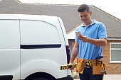 Builder With Van Texting On Mobile Phone Outside House