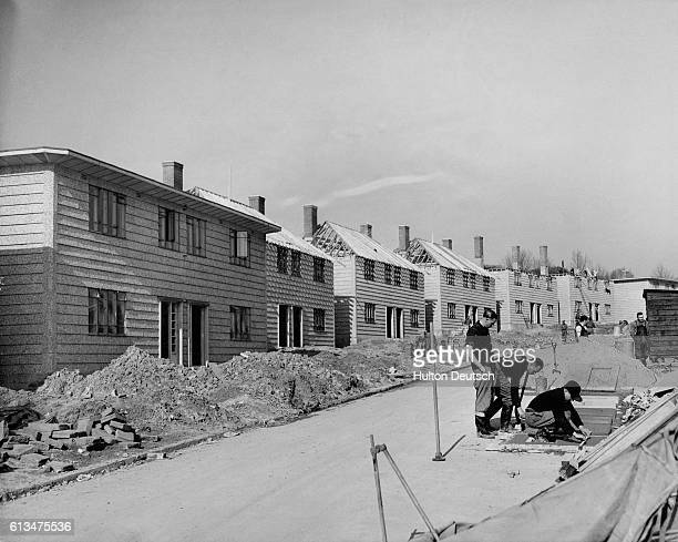 Builders at work in a unfinished street of semidetached Airey houses made from prefabricated concrete panels Some 20000 such houses are being built...