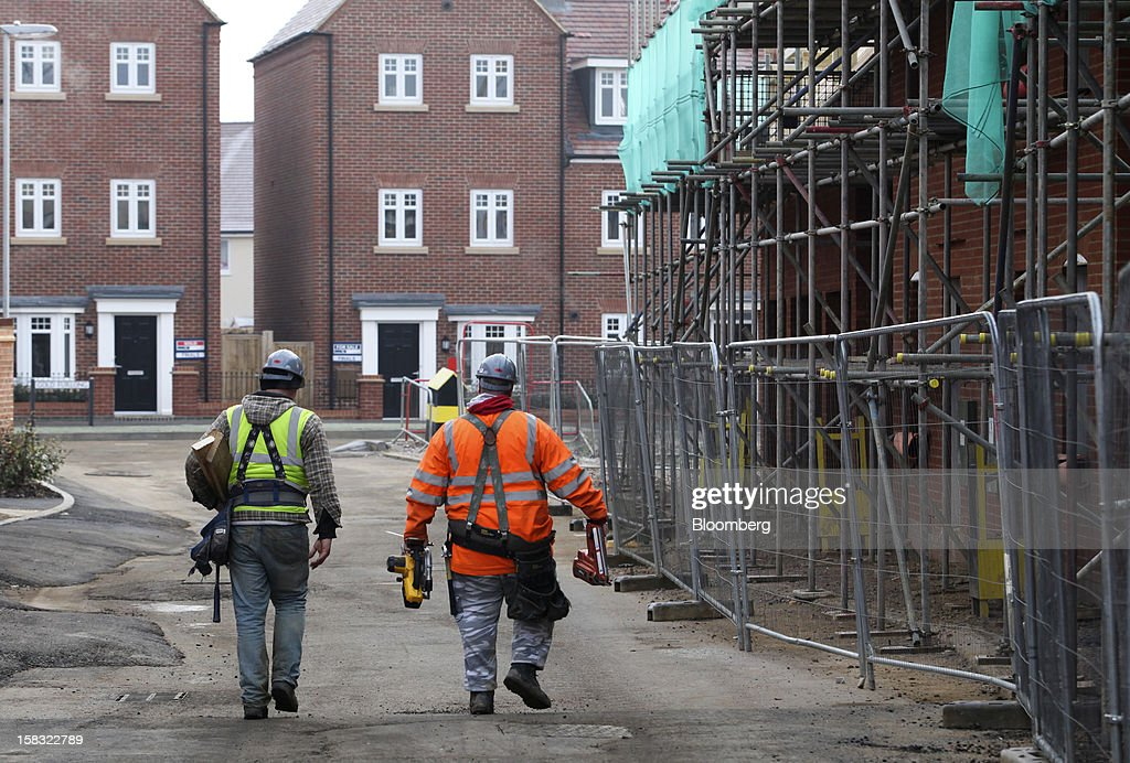 Builders carry their equipment as they pass safety fencing outside homes still under construction at a Barratt Developments Plc site for residential housing in Bedford, U.K., on Thursday, Dec. 13, 2012. Barratt Developments Plc, the U.K.'s largest homebuilder by volume, said advance sales rose 21 percent as government initiatives to boost homebuilding lifted private reservations in the autumn selling season. Photographer: Chris Ratcliffe/Bloomberg via Getty Images