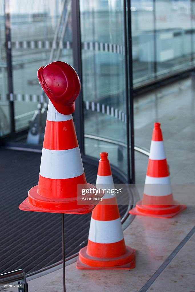 A builder's hard hat sits on a a traffic cone beside a doorway at the entrance of Berlin Brandenburg International Willy Brandt Airport in Schoenefeld, Germany, on Monday, May 3, 2016. The massively overbudget airport was planned to open in 2010 and handle 27 million passengers a year, crowning Berlin as the continent's 21st century crossroads. Photographer: Krisztian Bocsi/Bloomberg via Getty Images
