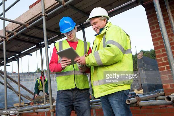 Builders Looking at a Digital Tablet