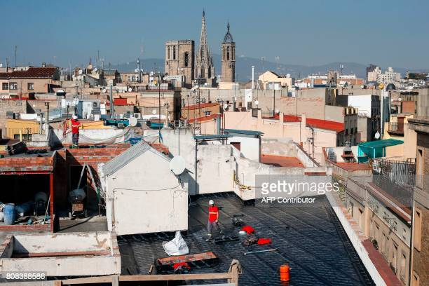 Builders work on a waterproof roof of a building of El Gotic neighborhood with the Cathedral in background in Barcelona on February 17 2017 Hordes of...
