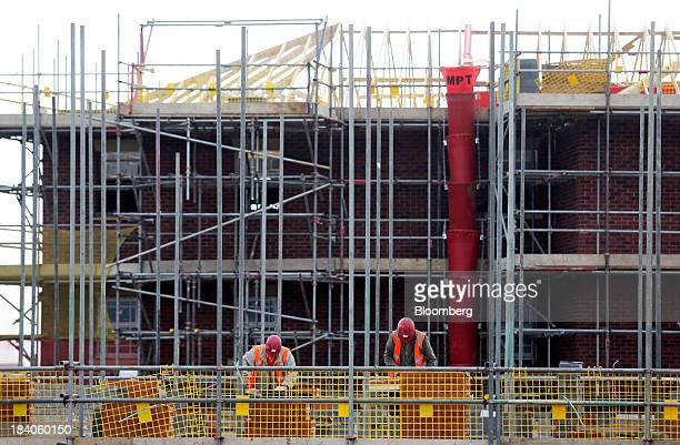 Builders work on scaffolding during construction at a Bellway Plc real estate site in Northampton UK on Thursday Oct 10 2013 UK house prices rose to...