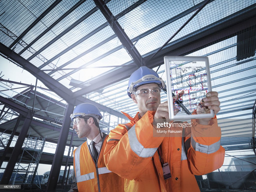 Builders working on plan details using digital tablet : Stock Photo