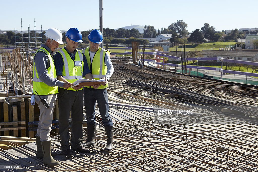 Builders working together on construction site : Stock Photo