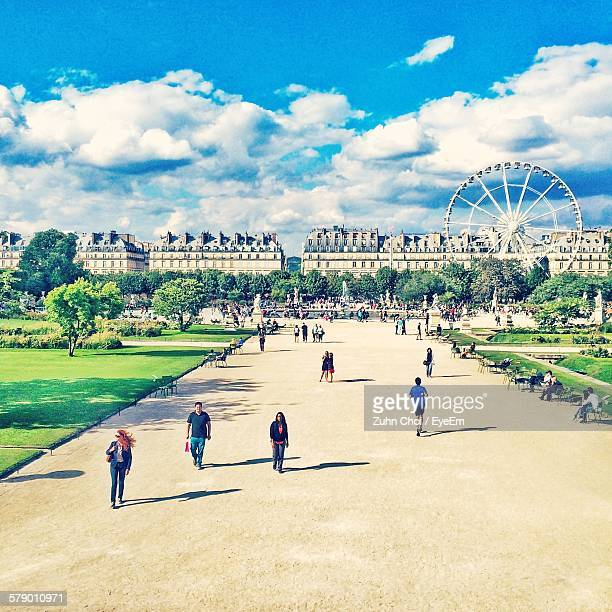 Building And Ferris Wheel In Front Of People Against Cloudy Sky In City At Tuileries Garden
