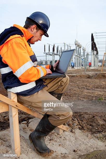 Building electricity substation, looking at laptop