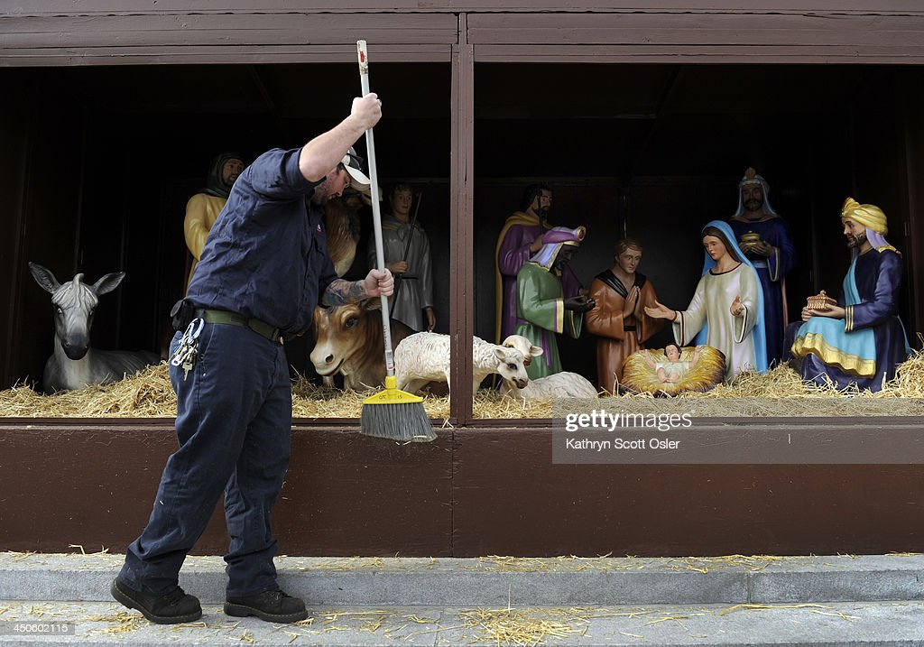 Building engineer Michael Spratt brushes off some of the extra hay as he and fellow crew members from the City and County of Denver place the figures inside the nativity scene in front of the City and County building in preparation for the upcoming holiday season.