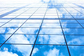 Building facade - glass and steel, sky with clouds, low angle view.