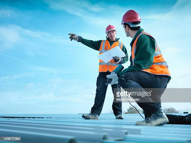Building foreman holding plans and directing apprentice on factory roof