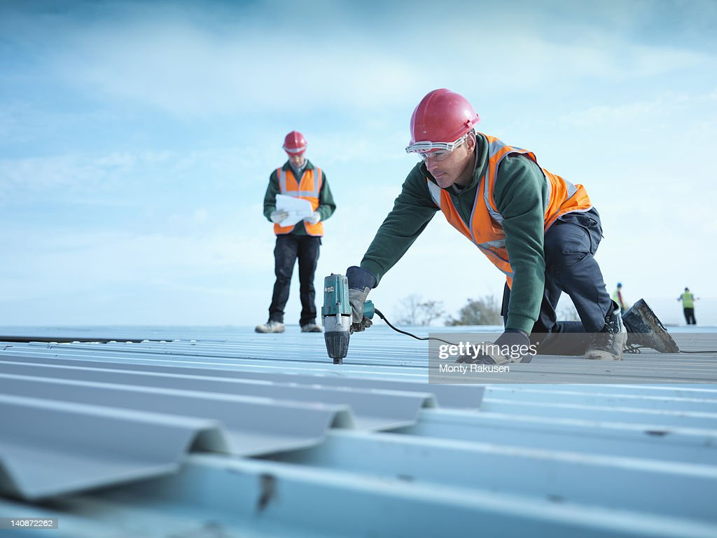 Building foreman reading plans as workman insulates factory roof