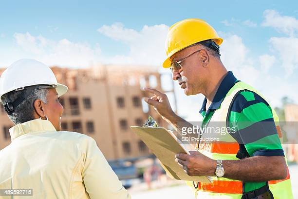 Building inspector pointing out something with construction