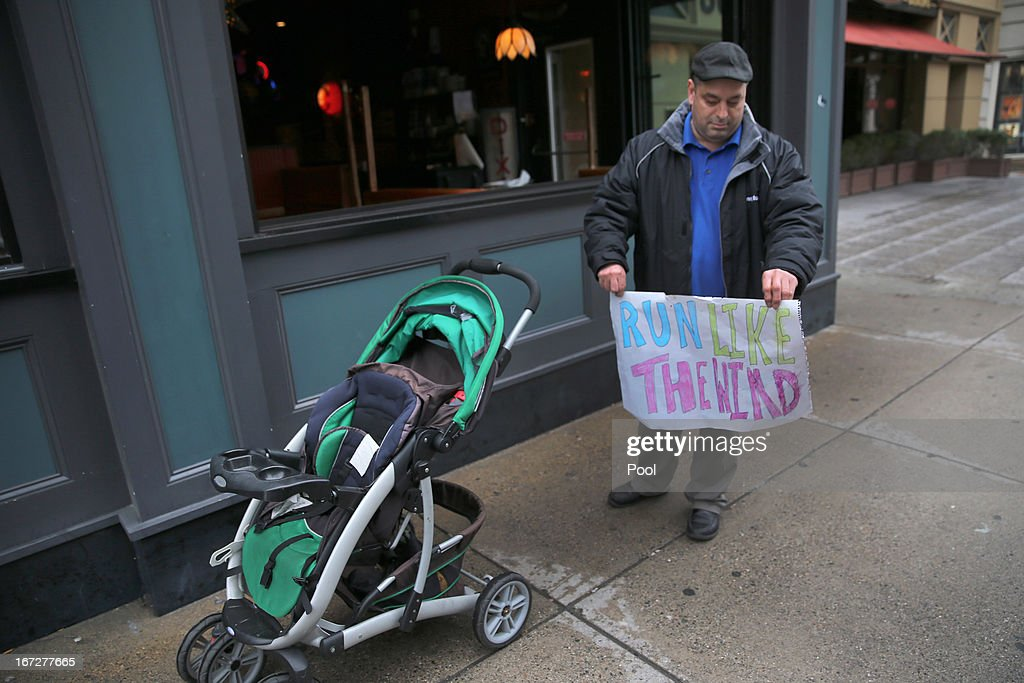 Building manager Candido Corchado holds a marathon sign next to the baby stroller of one of his tennants on April 23, 2013 in Boston, Massachusetts. The city conducted a final cleanup of Boylston Street and started opening the street to residents and business owners.