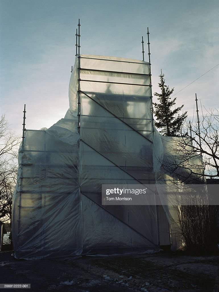 Building obscured by scaffolding and plastic sheets : Stock Photo