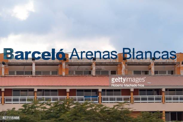 Building of Hotel Barcelo Arenas Blancas with chipped paint and red tilted roofs over balconies with trees in front