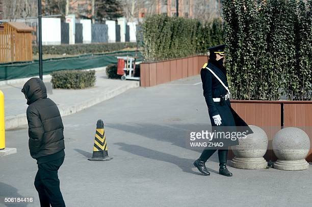 A building security guard braves a cold breeze as he stands guard in Beijing on January 22 2016 Schools have been suspended and emergency workers put...