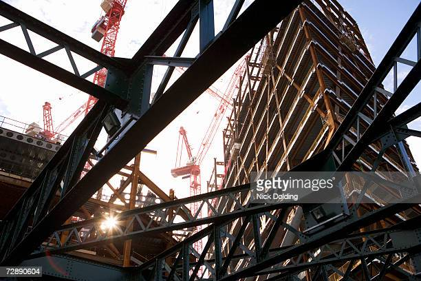 Building site with cranes, view through metal frame construction, low angle view