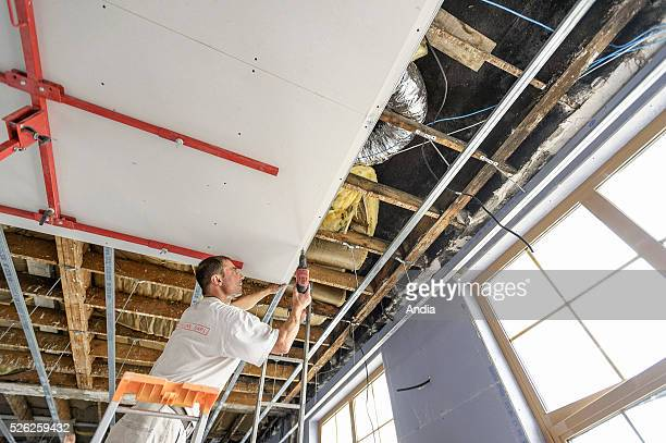 worker putting up plasterboard on a ceiling 2012