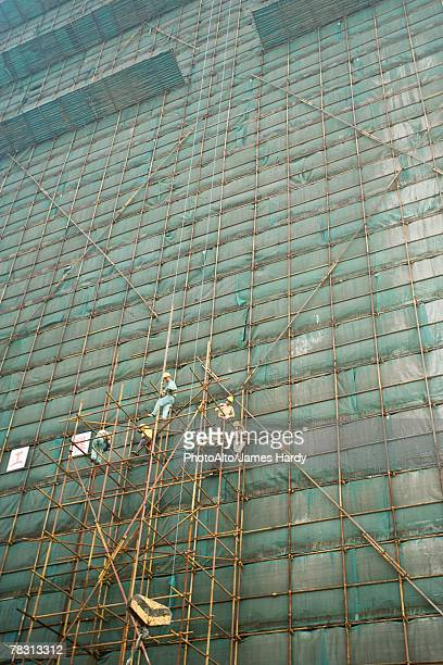 Building undergoing renovation, workers on scaffolding