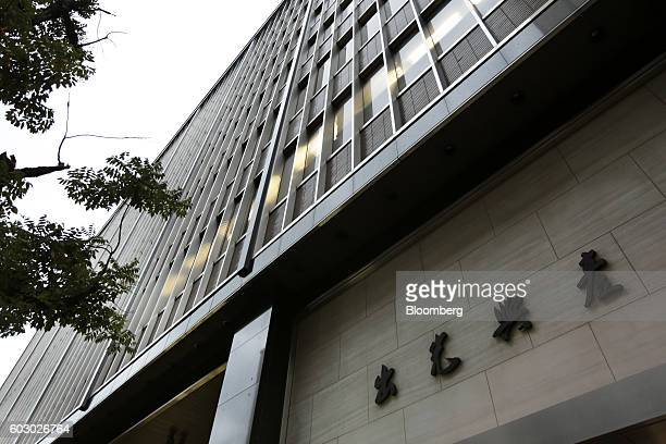 A building which houses the Idemitsu Kosan Co headquarters stands in Tokyo Japan on Wednesday Aug 10 2016 Attendants clean a customer's vehicle at an...