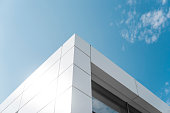 Building with white aluminum facade and aluminum panels against blue sky